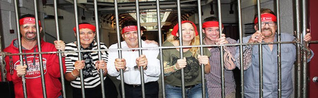 people behind jail bars in our Break out Team Building Activity