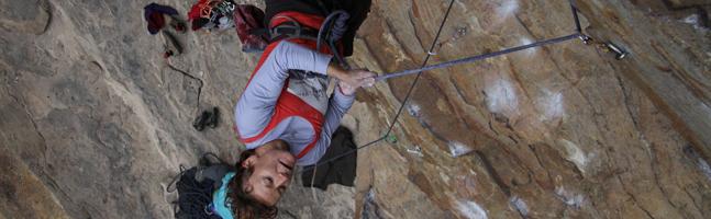Rock climbing team building activity - man hanging upside down