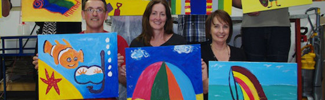 3 participants holding up the paintings they made in the Picasso art team building activity
