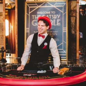 Host standing at the setup blackjack table - gatsby gamble evening team building activities
