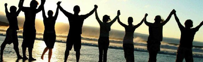 group holding hands together at sunset at the beach at the completion of a corporate team building event